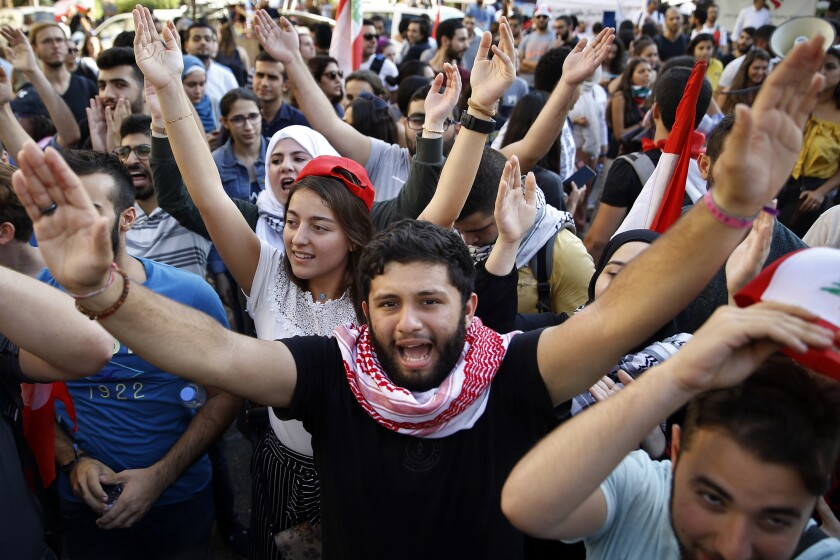University students chant slogans against the government, in Beirut, Lebanon, Tuesday, Nov. 12, 2019. Protesters in Lebanon resumed demonstrations on Tuesday blocking some roads and governmental institutions. (AP Photo/Bilal Hussein)