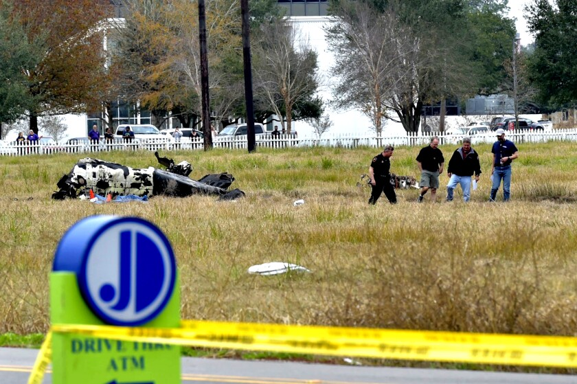 Investigators look over the site of a plane crash near Feu Follet Road and Verot School Road in Lafayette, La., on Saturday.