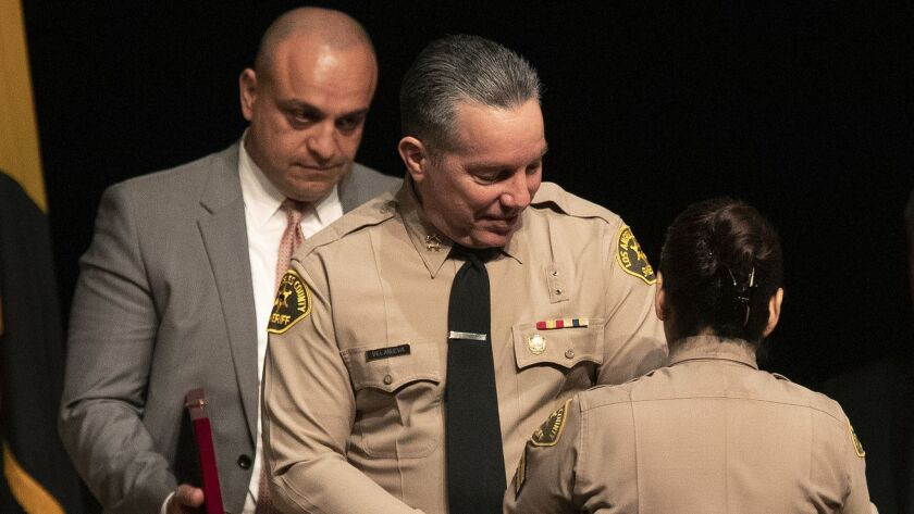 Los Angeles County Sheriff's Deputy Caren Carl Mandoyan, left, looks on as Alex Villanueva prepares to take the oath as Los Angeles County sheriff on Dec. 3, 2018.
