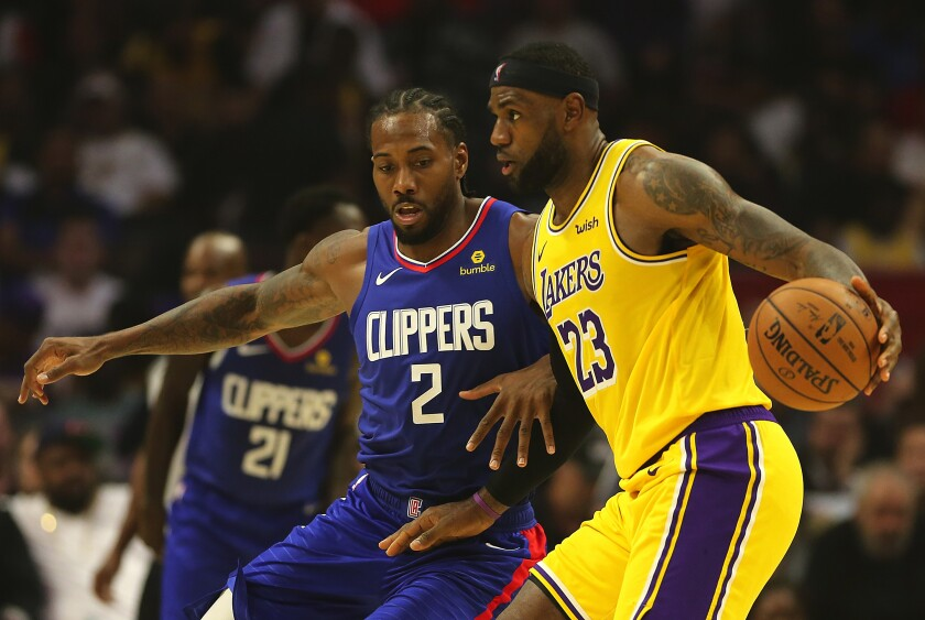 Clippers forward Kawhi Leonard, left, guards Lakers forward LeBron James.