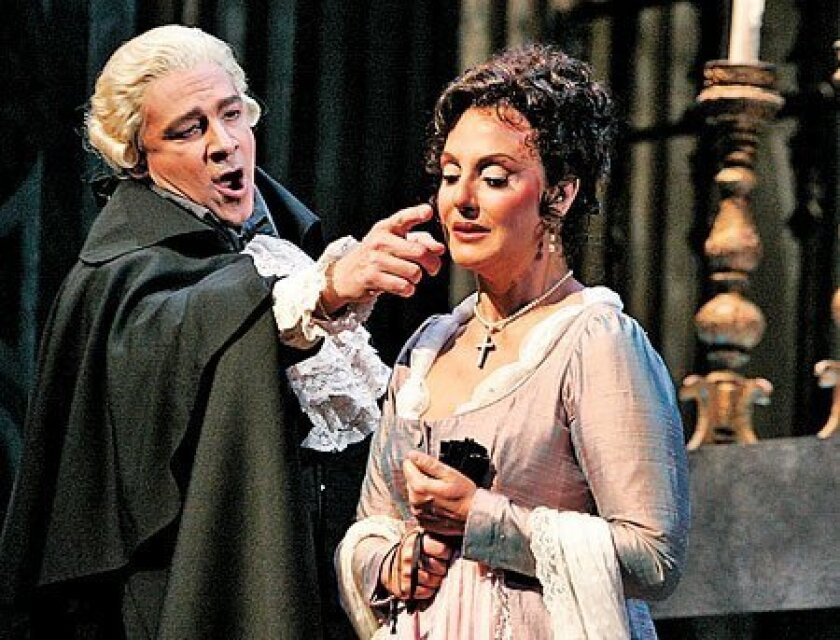As Scarpia, Greer Grimsley puts the moves on Sylvie Valayre's Tosca in Puccini's classic opera. (Peggy Peattie / Union-Tribune)