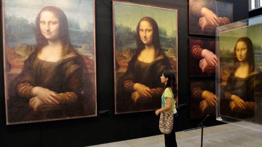 """A visitor looks at replicas of Leonardo da Vinci's Mona Lisa at the """"Da Vinci The Genius"""" exhibitio"""