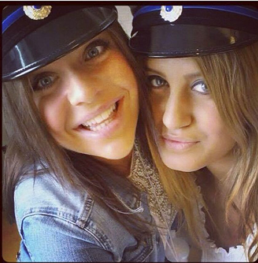 This June 10, 2012, photo shows Alexandra Mezher, right, and her friend Lejla Filipovic, left, when they graduated from high school in Boras Sweden. Mezher a 22-year-old worker at a shelter for youth and unaccompanied minors was stabbed to death at the center in southwestern Sweden on Monday Jan. 25, 2016. (Lejla Filipovic via AP)