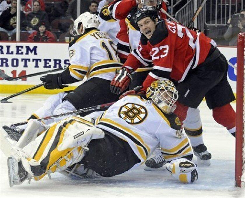 New Jersey Devils' David Clarkson (23) knocks over Boston Bruins goaltender Tim Thomas during the second period of an NHL hockey game Friday, Feb. 13, 2009 in Newark, N.J. (AP Photo/Bill Kostroun)