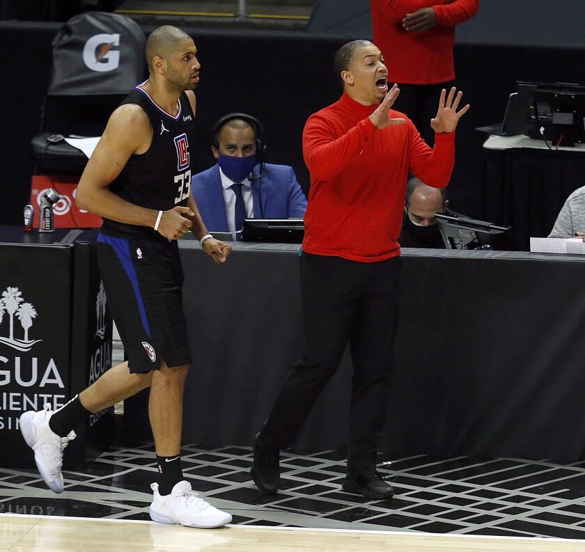 Clippers coach Tyronn Lue yells instruction as forward Nicolas Batum heads up court.