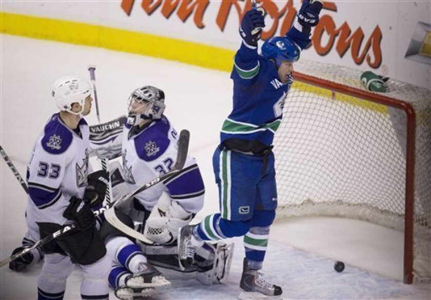 Vancouver Canucks left wing Raffi Torres (13) celebrates teammate Christian Ehrhoff's goal against Los Angeles Kings goalie Jonathan Quick (32) as Kings Willie Mitchell looks on during second period NHL hockey action at Rogers arena in Vancouver, British Columbia, Thursday, March 31, 2011.  (AP Pho