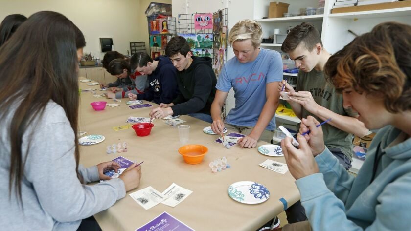 Sage Hill School sophomore students from Kate Ball's Modern World History class paint ceramic butter