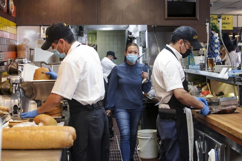 Trabajadores enmascarados preparan comidas en la cocina de Langer's Deli en Los Ángeles el martes.