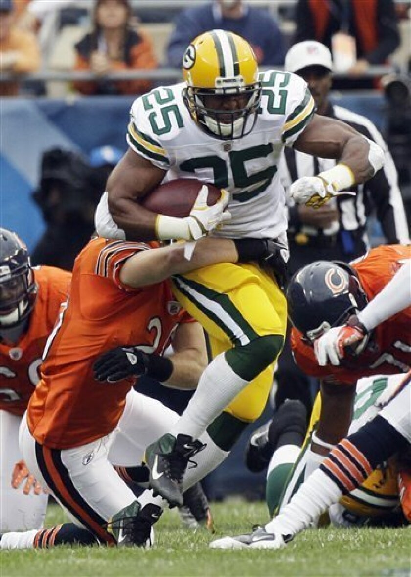 Green Bay Packers running back Ryan Grant (25) is tackled by Chicago Bears safety Craig Steltz (20) in the first half of an NFL football game in Chicago, Sunday, Sept. 25, 2011. (AP Photo/Nam Y. Huh)