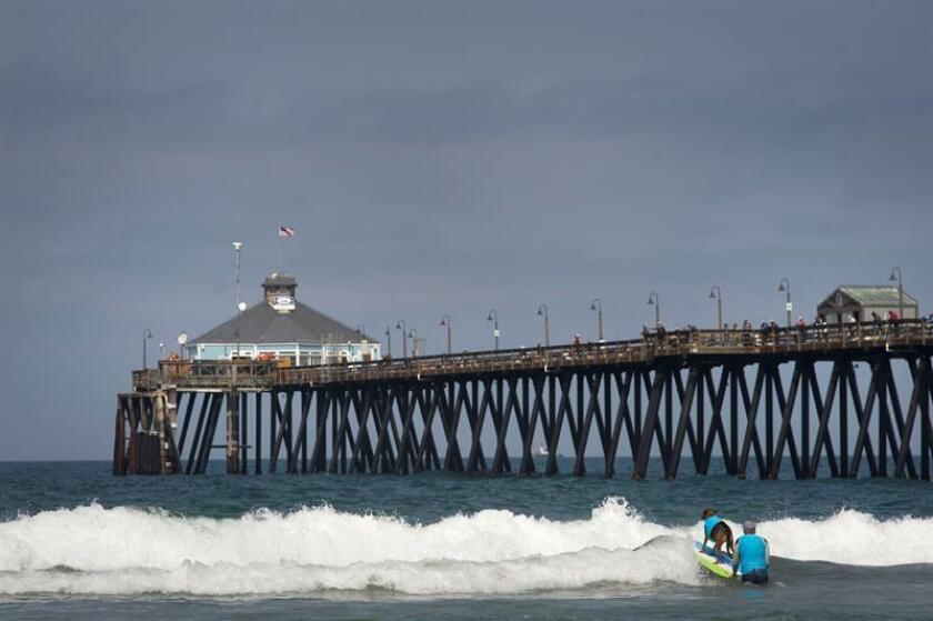 Vista de un hombre que empuja la tabla de surf con su perro a bordo en una playa de San Diego. EFE/Archivo
