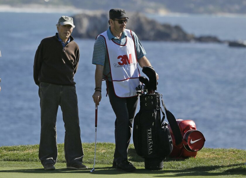 Actor/director Clint Eastwood, left, stands with his caddie Nick Faldo, right, while waiting to putt on the 18th green of the Pebble Beach Golf Links during the celebrity challenge event of the AT&T Pebble Beach National Pro-Am golf tournament Wednesday, Feb. 10, 2016, in Pebble Beach, Calif. (AP P