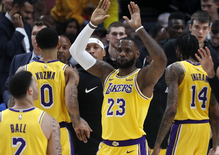 LeBron James celebrates a basket by teammate Lonzo Ball during his regular-season debut with the Lakers on Oct. 19, 2018.