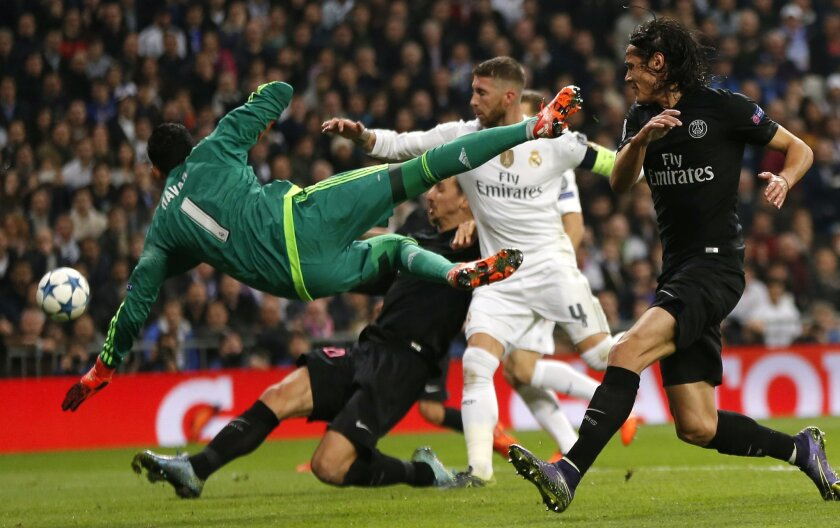 Real Madrid goalkeeper Keylor Navas saves a goal by PSG's Edinson Cavani, right, during their Group stage of Champions League Group A soccer match at the Santiago Bernabeu stadium in Madrid, Spain, Tuesday, Nov.3, 2015. (AP Photo/Daniel Ochoa de Olza)