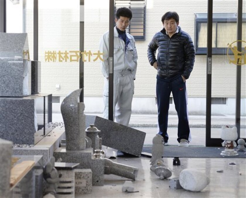Men look at fallen gravestones at a stone shop following an earthquake in Awaji, Hyogo prefecture, western Japan, Saturday, April 13, 2013.  Japan's Meteorological Agency said a magnitude-6 quake has struck near the southwestern city of Kobe, but public broadcaster NHK reports there is no major dam