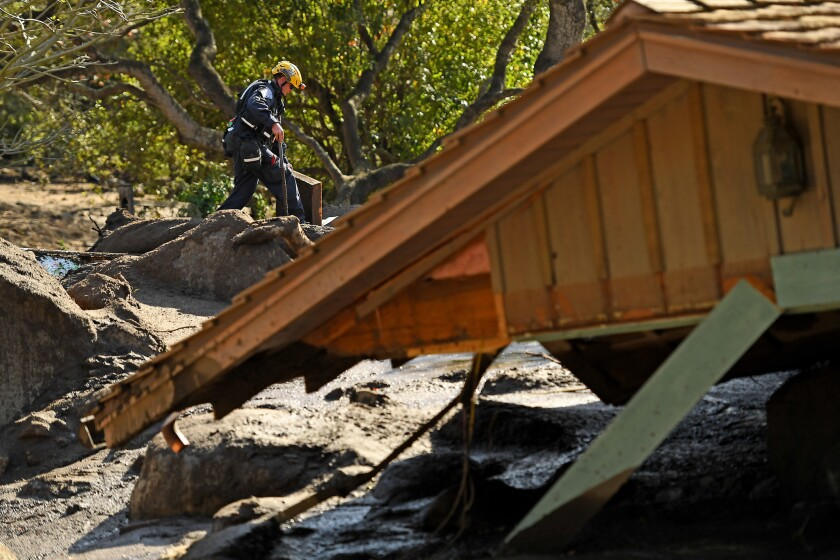 A member of a search-and-rescue team inspects property near a home on Glen Oaks Drive in Montecito.
