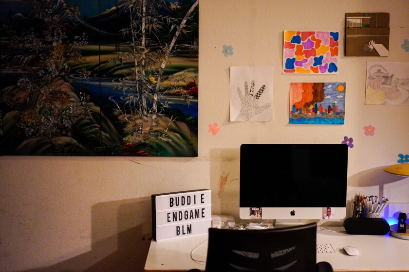 A sign next to a computer on a teenager's desk says Buddie endgame BLM