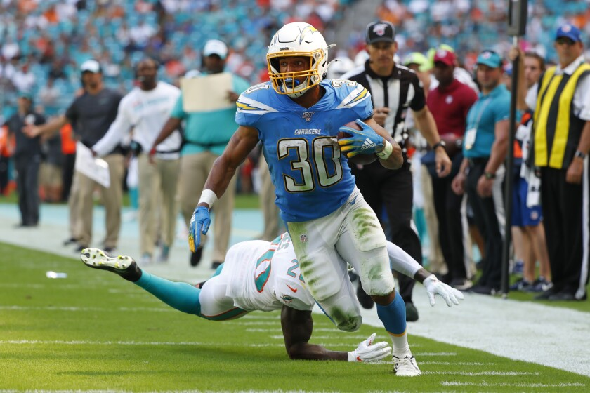 Chargers running back Austin Ekeler evades Dolphins safety Reshad Jones on an 18-yard touchdown pass play Sunday.