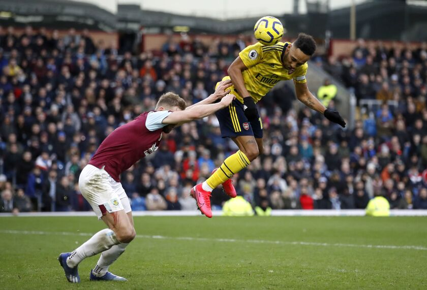 Arsenal's Pierre-Emerick Aubameyang, right, and Burnley's Ben Mee battle for the ball during the English Premier League soccer match at Turf Moor, Burnley, England, Sunday Feb. 2, 2020. (Martin Rickett/PA via AP)