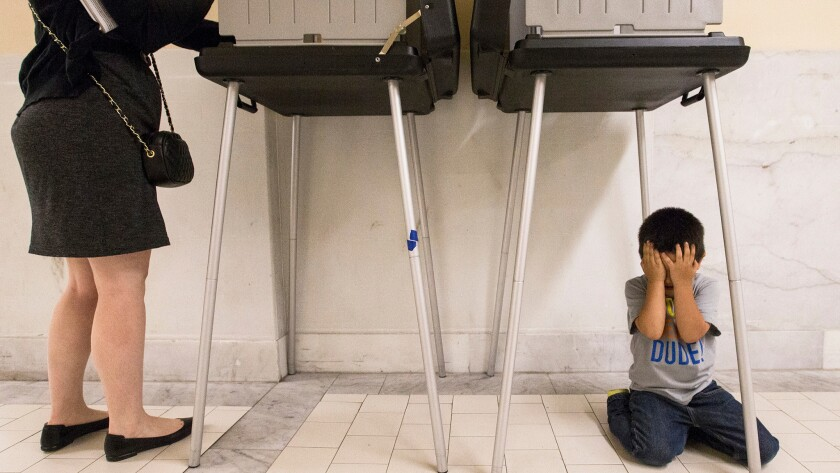 Johnny Lucero, 3, plays underneath a polling box while his mother, Nicanora Contreras, casts her vote Tuesday at San Francisco City Hall.