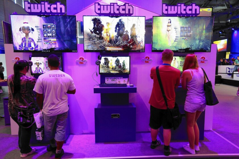 Visitors stream online computer games on the Twitch Interactive stand at a video games fair in Cologne, Germany, this month.