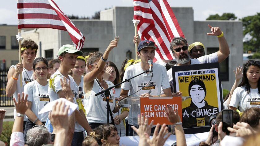 David Hogg, center, a survivor of the school shooting at Marjory Stoneman Douglas High School in Parkland, Fla., addresses a rally in front of the headquarters of gun manufacturer Smith & Wesson in Springfield, Mass.
