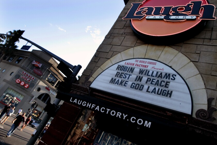 Tourists walk past the Laugh Factory on Sunset Boulevard, where the marquee pays tribute to Robin Williams.
