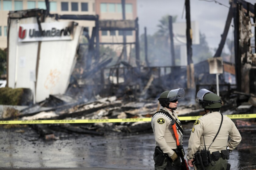 San Diego County sheriff officers stand guard in front of a burning bank building after a protest over George Floyd's death on Sunday in La Mesa, Calif.