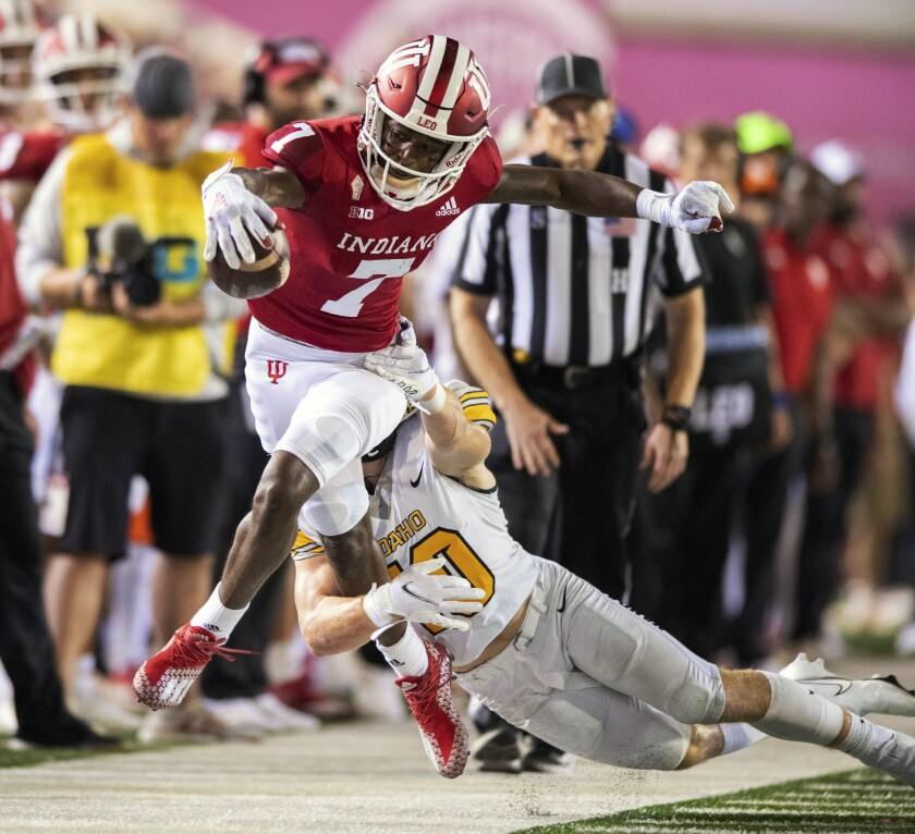 Indiana wide receiver D.J. Matthews Jr. (7) attempts to stretch his run for a first down as he's knocked out-of-bounds by Idaho linebacker Coleman Johnson (10) during the first half of an NCAA college football game, Saturday, Sept. 11, 2021, in Bloomington, Ind. (AP Photo/Doug McSchooler)