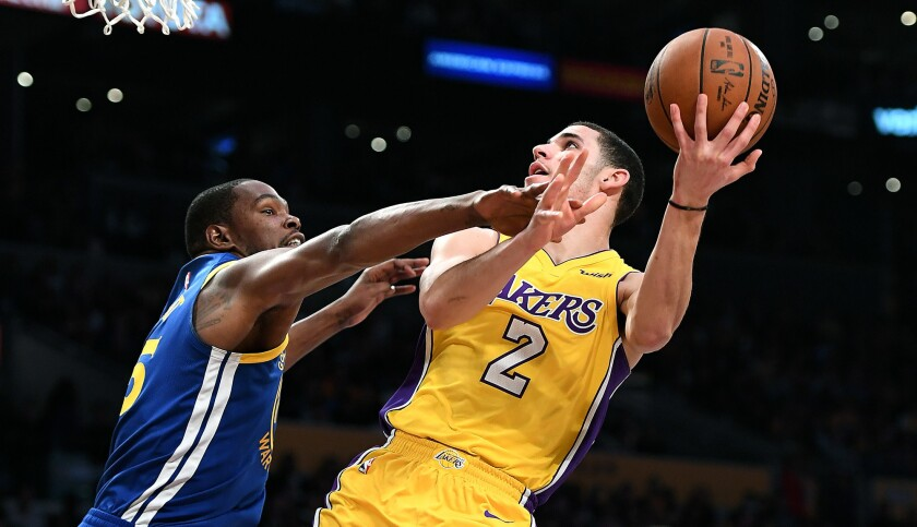 LOS ANGELES, CALIFORNIA DECEMBER 18, 2017-Lakers Lonzo Ball is fouled by Kevin Durant while driving