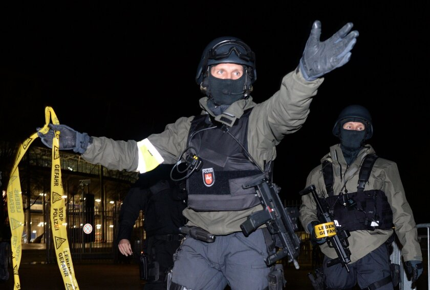 Police officers carry guns outside the HDI-Arena in Hannover, Germany, Tuesday, Nov. 17, 2015. The international friendly between Germany and Holland match was called off at short notice and the stadium was evacuated. (Julian Stratenschulte/dpa via AP)