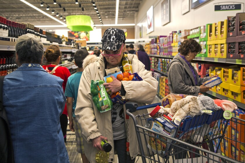 Janelle Myers of Riverside fills her arms with groceries while searching for her shopping basket in the crowds during the grand opening of Aldi in Moreno Valley on Thursday.