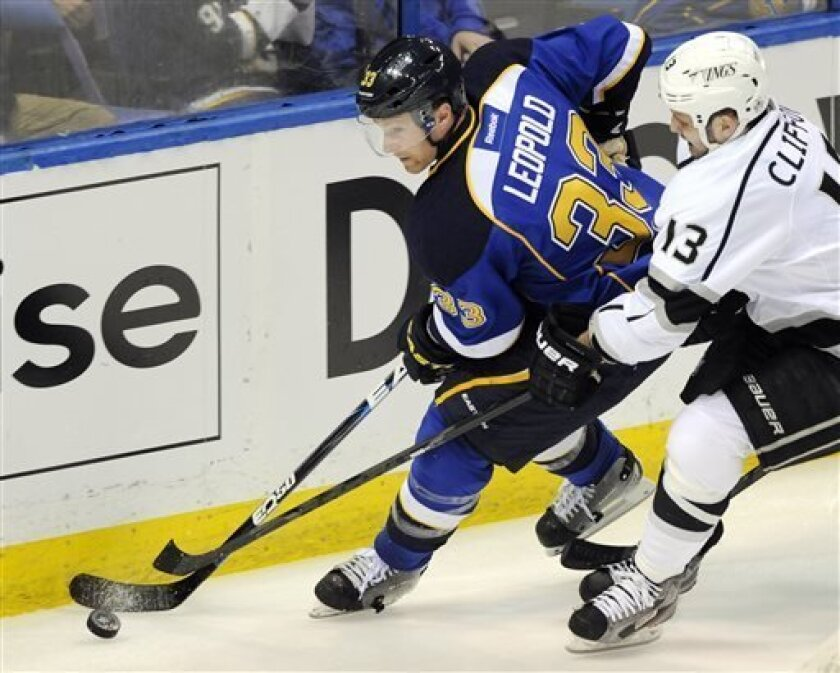 St. Louis Blues' Jordan Leopold (33) and Los Angeles Kings' Kyle Clifford (13) reach for the puck during the second period of Game 1 of their first-round NHL hockey Stanley Cup playoff series, Tuesday, April 30, 2013, in St. Louis. (AP Photo/Bill Boyce)