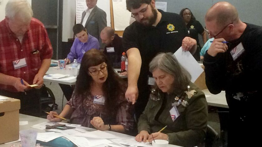 Election officials in Newport News, Va., examine ballots by hand during a recount for a House of Delegates race.