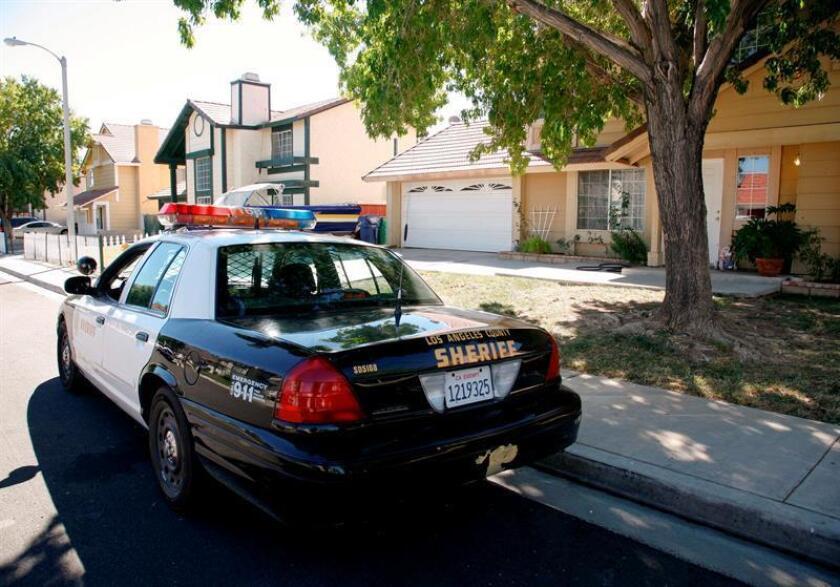 Un coche patrulla permanece aparcado frente al domicilio de un miembro de un grupo de hispanos formado por seis adultos y 8 niños residentes en Palmdale (California, EE.UU.) EFE/Archivo