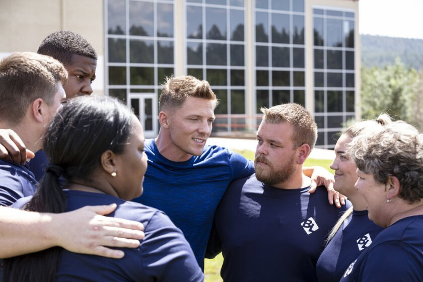 """The Biggest Loser"" trainer Steve Cook, center, talks with participants."