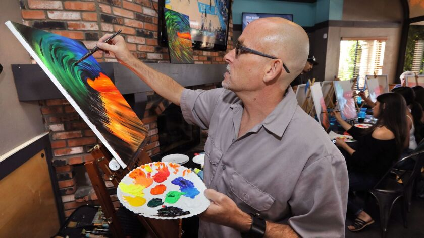 Artist Al Scholl works on his painting of a colorful wave as he teaches his Art Therapy class at the Inland Tavern.