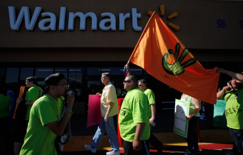 "Wal-Mart worker Anthony Goytia carries an ""our Wal-Mart"" flag outside a Paramount store alongside some 200 employees and supporters who protested for better working conditions, higher salaries and no retaliation for those who speak out against the company."