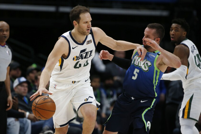 Utah Jazz forward Bojan Bogdanovic (44) tries to get away from Dallas Mavericks guard J.J. Barea (5) during the first half an NBA basketball game in Dallas, Monday, Feb. 10, 2020. (AP Photo/Michael Ainsworth)
