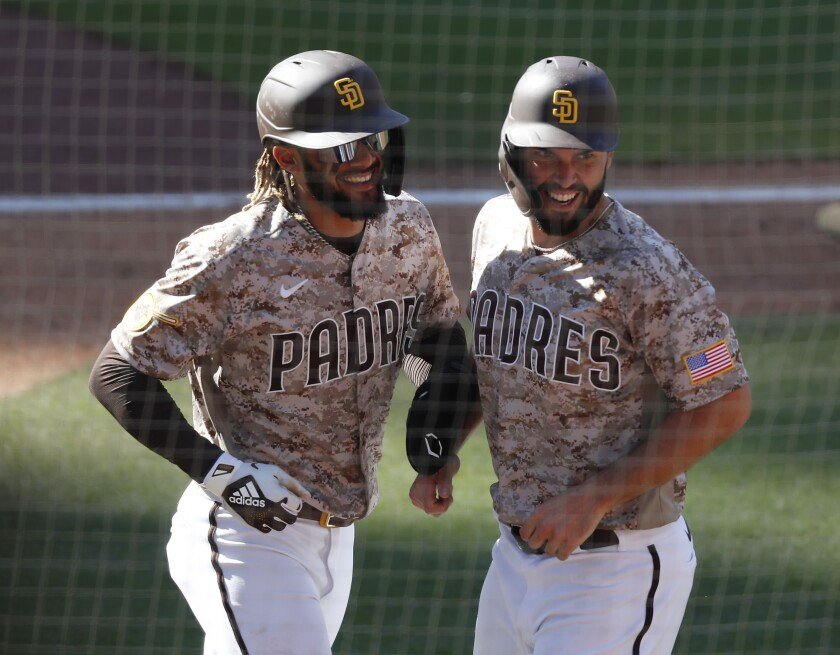 Padres teammates Fernando Tatis Jr. and Eric Hosmer celebrate after scoring.