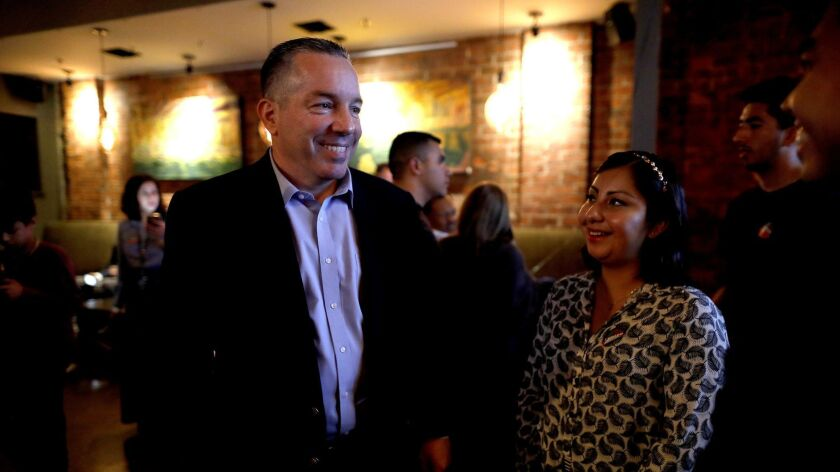 Retired Sheriff's Lt. Alex Villanueva, left, gathers with supporters on election night at Cities Restaurant in Los Angeles. He held a razor-thin lead over incumbent Sheriff Jim McDonnell.