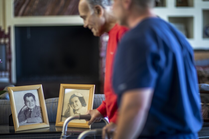 Robert Borns exercises in a living room filled with family photos