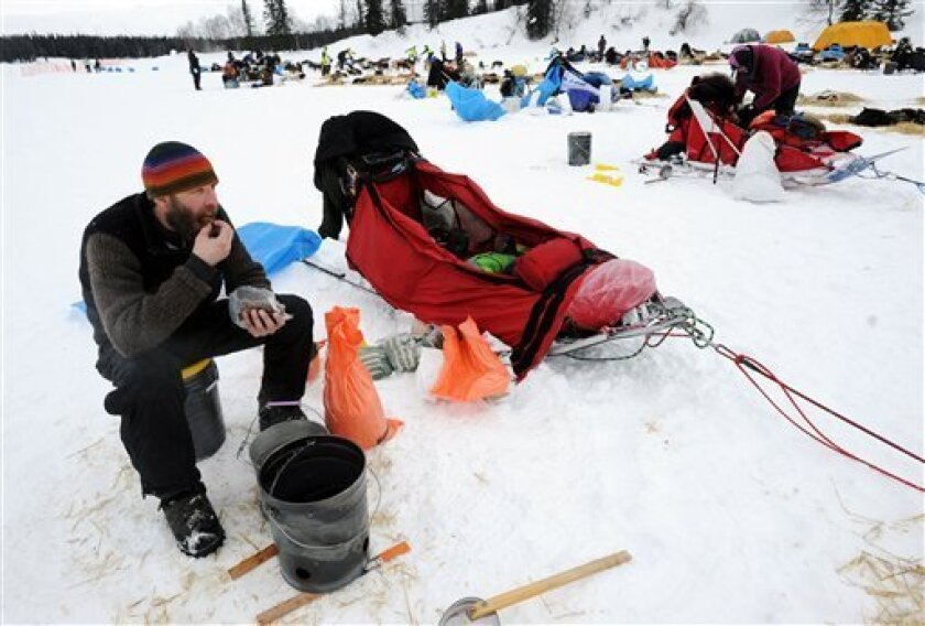 Mike Ellis eats breakfast while resting his dog team at the Finger Lake checkpoint in Alaska during the Iditarod Trail Sled Dog Race on Monday, March 4, 2013. (AP Photo/The Anchorage Daily News, Bill Roth)