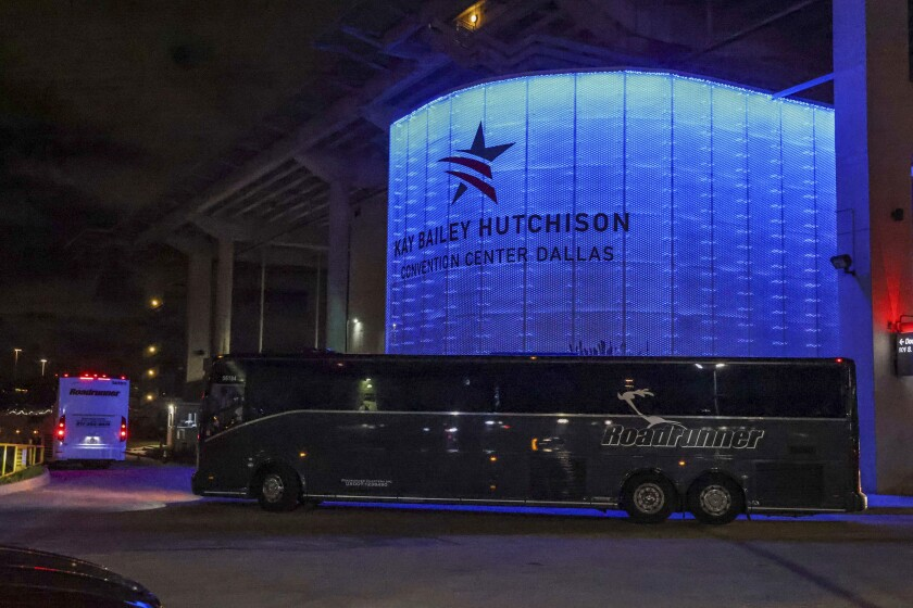 Charter buses arrive at the Kay Bailey Hutchison Convention Center in Dallas, escorted by the Federal Protective Service.