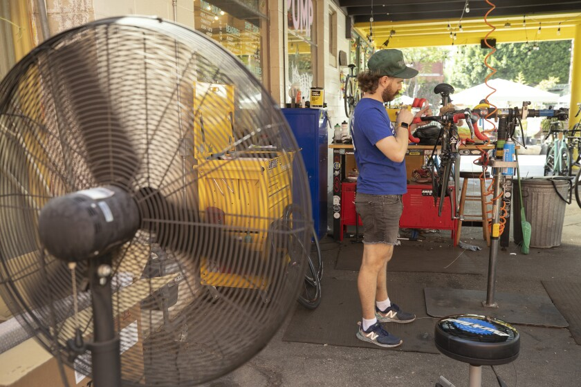 A man works on a bicycle lifted up on a stand outside a bike shop