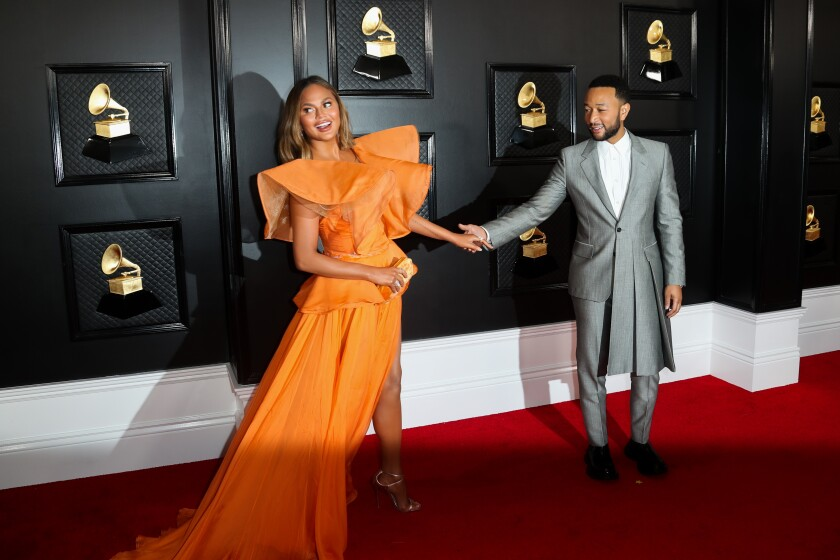 A woman in an orange dress and a man in a silver suit