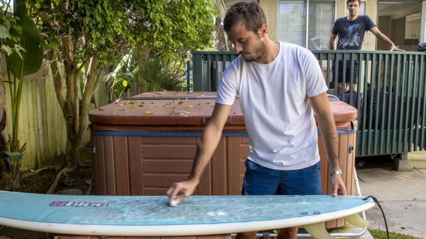Jeremy Berjeaud waxes a surfboard as Thomas Vaccargiu looks on before a surf session at their Outsite house in Encinitas