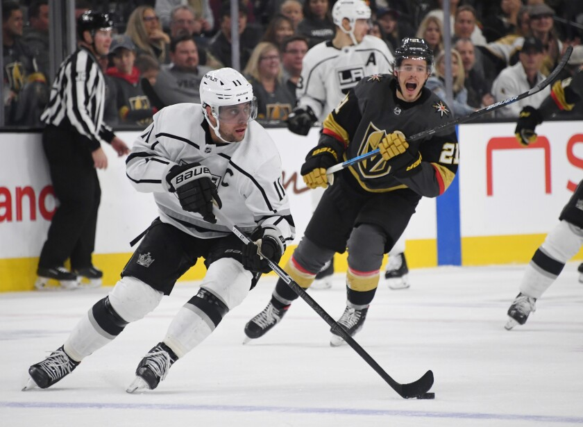 Kings captain Anze Kopitar controls the puck ahead of Vegas Golden Knights forward Nick Cousins during the Kings' 4-1 win Sunday.