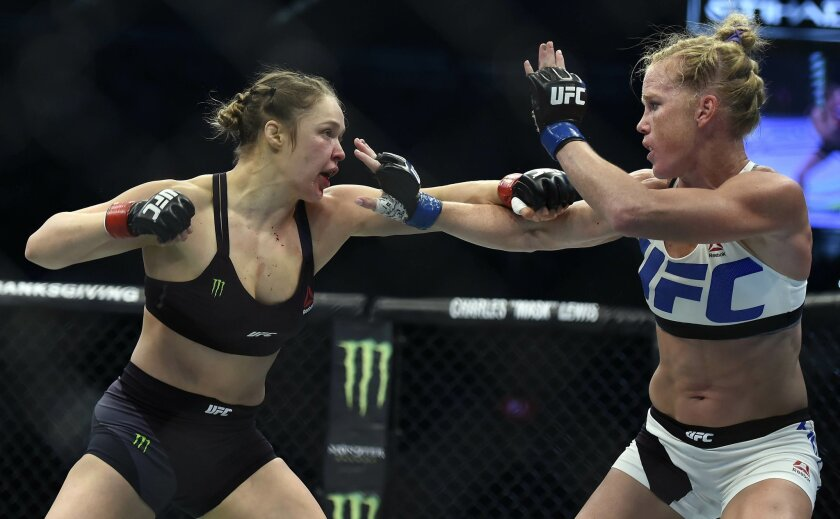 FILE - In this Sunday, Nov. 15, 2015 file photo, Ronda Rousey, left, and Holly Holm fight during their UFC 193 bantamweight title bout in Melbourne, Australia. Holm pulled off a stunning upset victory over Rousey in the fight, knocking out the women's bantamweight champion in the second round with
