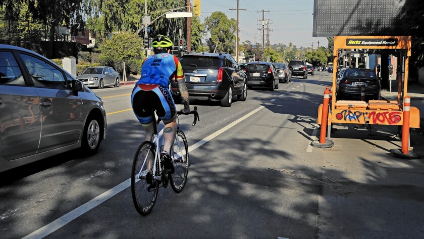 A cyclist rides alongside vehicle traffic on Rowena Avenue in Silver Lake. The city's Mobility Plan 2035 would add hundreds of miles of bicycle and bus-only lanes.