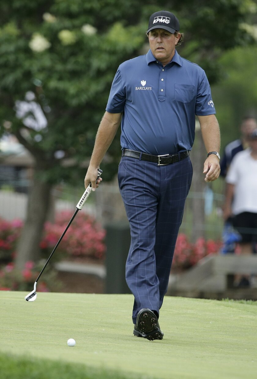 Phil Mickelson watches his putt on the ninth green during the third round of the Memorial golf tournament, Saturday, June 4, 2016, in Dublin, Ohio. (AP Photo/Darron Cummings)